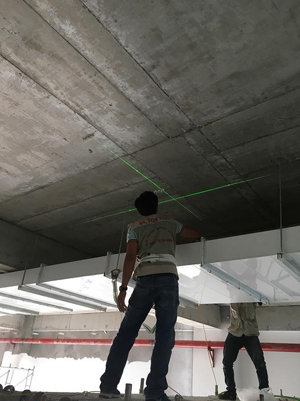 MNS dùng thiết bị Laser canh đường thẳng để thi công dây cho Camera an ninh.